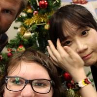 Fotoaufgabe: 3 Gruppenmitglieder um einem Weihnachtsbaum